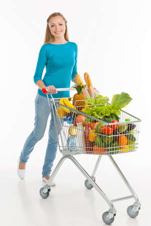 full shopping cart: Shopaholic. Cheerful young woman carrying shopping cart full of goods and smiling while isolated on white