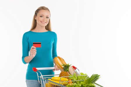 carro supermercado: Mujer en el supermercado. Alegre joven de pie cerca de la cesta de compras y de la tarjeta de crédito, mientras que aislados en blanco Foto de archivo