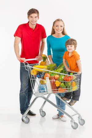 ni�os de compras: Compras de la familia. Familia alegre de pie cerca de cesta de la compra y sonriendo mientras aislados en blanco