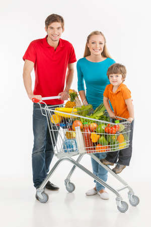 full shopping cart: Family shopping. Cheerful family standing near shopping cart and smiling while isolated on white