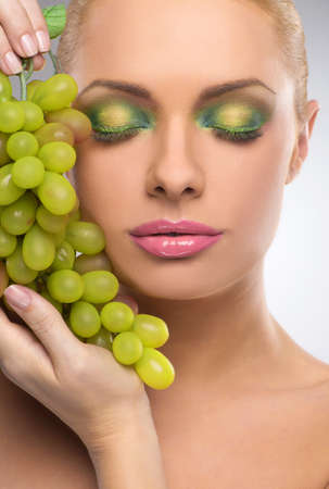 naked body: Beauty with grape. Portrait of beautiful women with make-up holding grape while isolated on grey Stock Photo