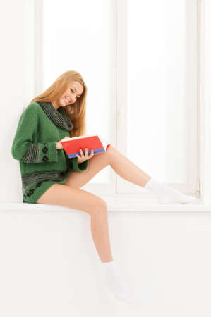 Reading book. Beautiful young woman reading book while sitting on the windowsill
