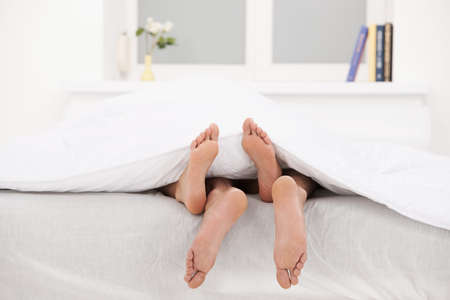Loving couple in bed  Close-up of human legs stretching out of the bed photo