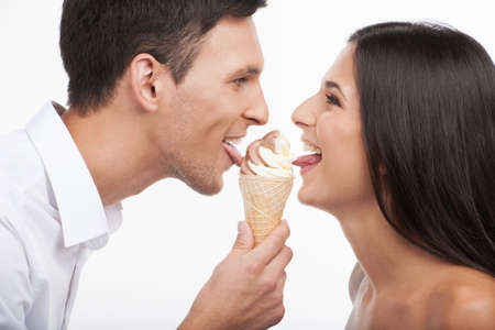 finger licking: Loving couple. Beautiful young loving couple looking at each other and eating ice-cream while isolated on white