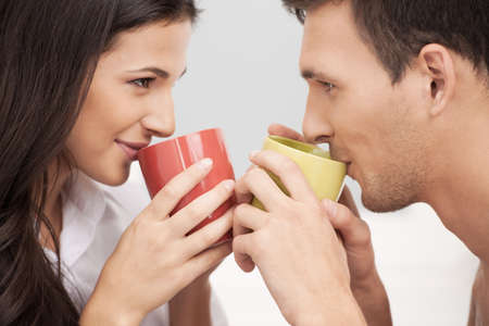 heterosexual couple: Loving couple. Beautiful loving couple looking at each other and drinking coffee Stock Photo