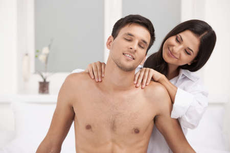 Loving couple. Beautiful young woman making massage for her boyfriend photo