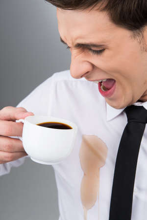 Man is spilling coffee on white shirt while drinking