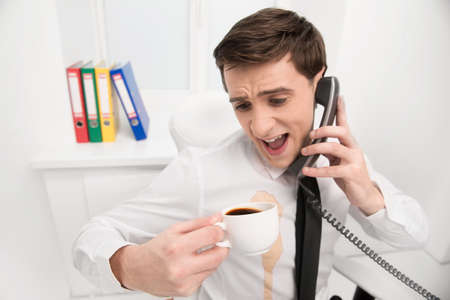 Man is spilling coffee on white shirt while drinking in office and talking by phone