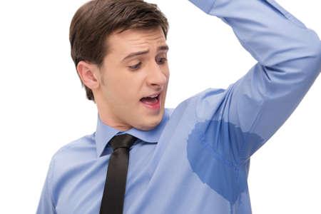Jonge man is veel zweten. Kijkend met verrassing op vlek op een shirt