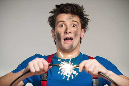 backgraound: Man has problems with electrical cable Stock Photo