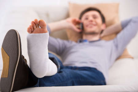 cast: Man is laying on sofa and talking by phone with bandage on leg Stock Photo