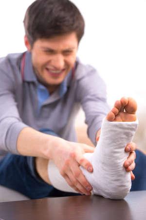 pierna rota: El hombre sufre de dolor mientras se toca la pierna rota Foto de archivo
