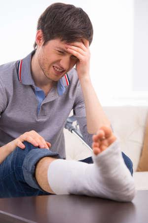 fractura: El hombre es molesto y sentir dolor por fractura de pierna en el vendaje