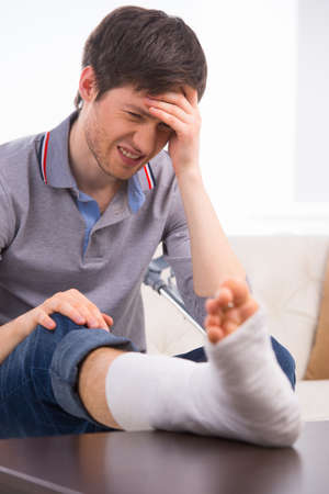 Man is upset and feel pain because of broken leg in bandage