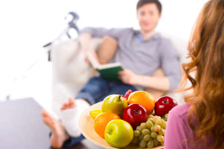 adult bones: Young couple, girl treats a man with fruit while he sitting with broken leg on beckground Stock Photo