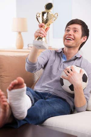 pierna rota: Hombre recordando buenos momentos ganadores partidos de fútbol. Ahora su pierna se Brocken