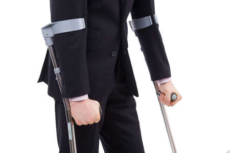 Businessman in a suit holding crutches. Isolated on white photo