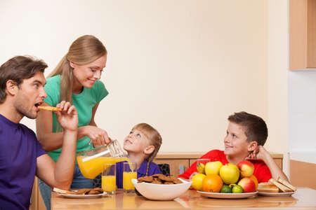 niños platicando: Madre está vertiendo naranja juicein un vaso para su hijo Foto de archivo