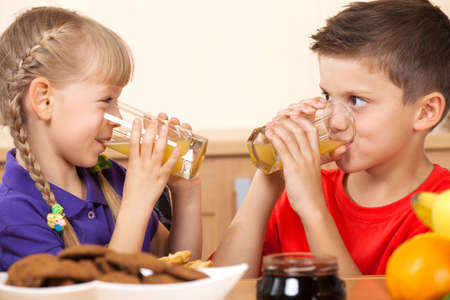 2 persons only: Two kids drink orrange juice while looking on each other