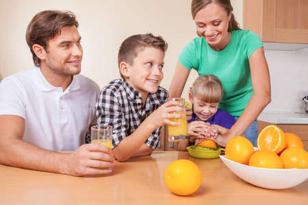 Famili is waiting for orange juice while mother and daughter is squeezing juice photo
