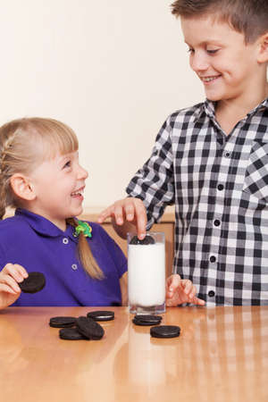 boys only: Two small kids playing with milk and cookies and milk Stock Photo
