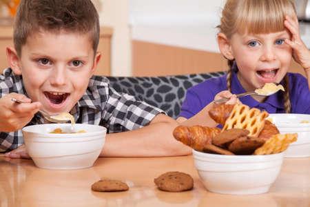niños desayunando: Dos niños están comiendo copos con leche, mientras que mirando a la cámara
