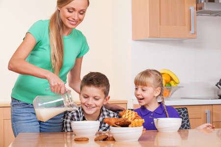 2 persons only: Mother is pouring milk to her son plates to cook flakes for him Stock Photo
