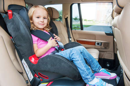 belts: Small girl is sitting in child cat seat, looking at the camera