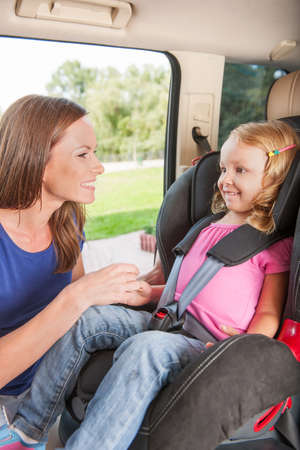 car seat: Mother helps her daughter to fasten belt on car seat Stock Photo
