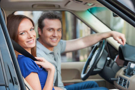 Loving couple in a car looking in camera, toothy smile photo