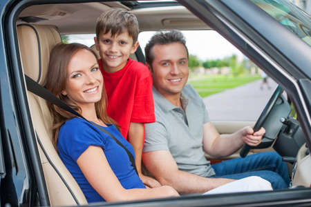 Family with one kid is travelling by car, smiling and looking at camera photo