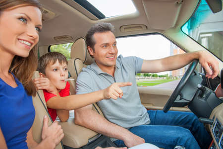 transport interior: Boy is pointing his finger on something while sitting a car with his family Stock Photo