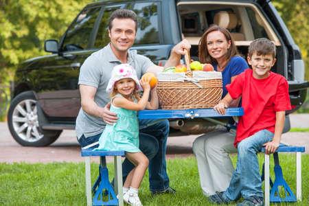 family picnic: Familia con dos hijos en la comida campestre, sentado junto a la mesa con cesta de frutas