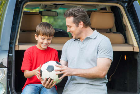 Father and son sit near car with opened boot and going to talk about football game photo
