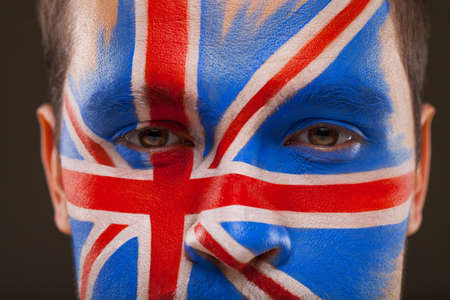 rooting: Close-up of face with face art on it. Flag of Great Britain on black