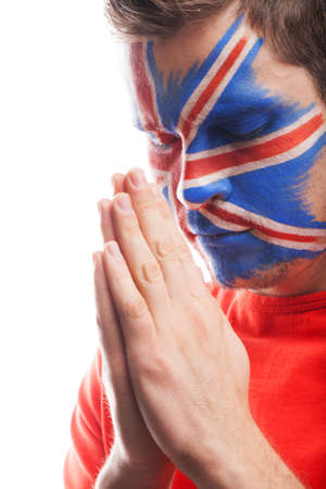 Man with face art prays for his team to be a winner photo