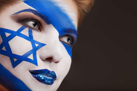Girl with Face art. Israel flag painted on a face. photo