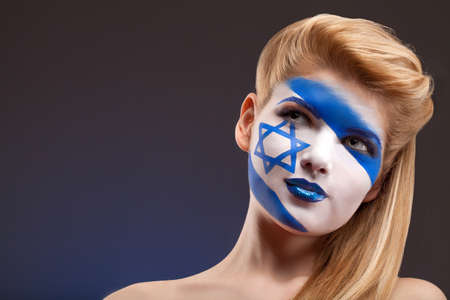 rooting: Face art. Blond girl with painted face looking up