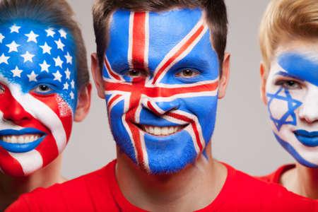 caritas pintadas: Primer plano de las caras pintadas. Tres persona con bandera contries diffrent pintado en sus rostros