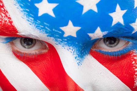 Primer plano de los ojos. Cara pintada con la bandera de EE.UU. mirando a la cámara