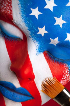 pintura en la cara: Cara de la mujer que se pinta. EE.UU. bandera es la pintura con pincel, close-up