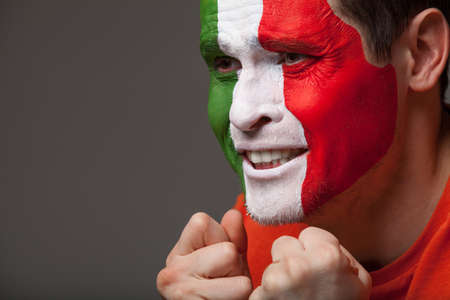 soccer fan: Italian fan. With painted face is rooting for his team with sad emotions on his face