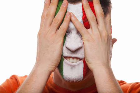 man face close up: Man with painted face covers face with hands. Close up isolated on white