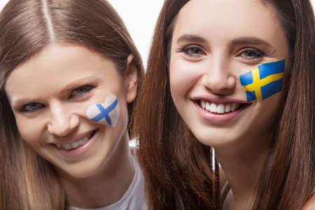 Two girls with painted flags on their face. With flag of Finland and flag of Sweden. Looking at the camera and smile photo