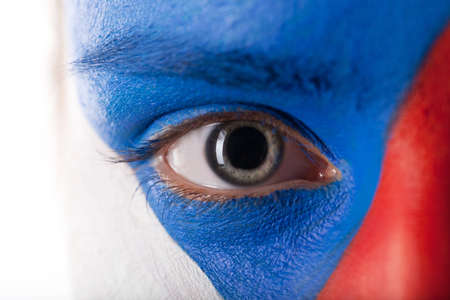 dilated pupils: Close up of eye with dilated pupil. Face is painted in blue, red and white colors Stock Photo