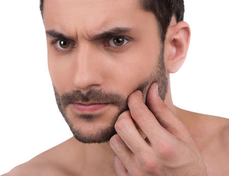 stubble: Close up of mans unshaven face. Man touches his skin
