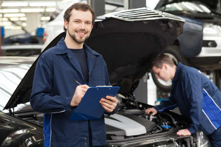 auto focus: Mechanics at repair shop. Cheerful young mechanic writing something in his clipboard while another one fixing a car on the background