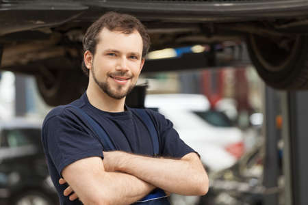 car shop: He is confident in his work. Young confident mechanic standing with his arms crossed and looking at camera