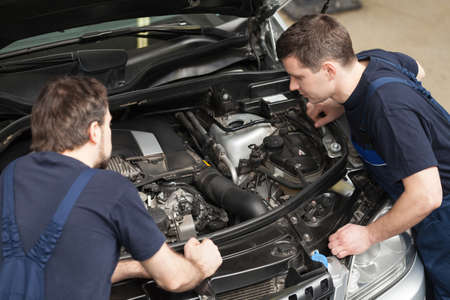 auto mechanic: Mechanics at repair shop. Top view of two confident mechanics working on a car engine