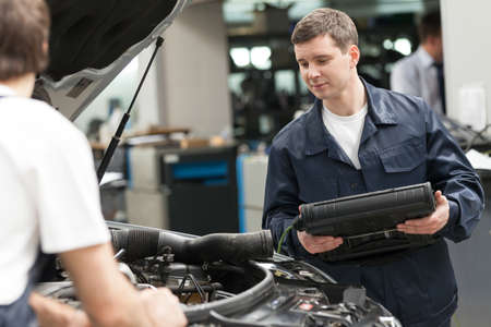 auto shop: Mechanics at work shop. Two confident auto mechanics working at the repair shop